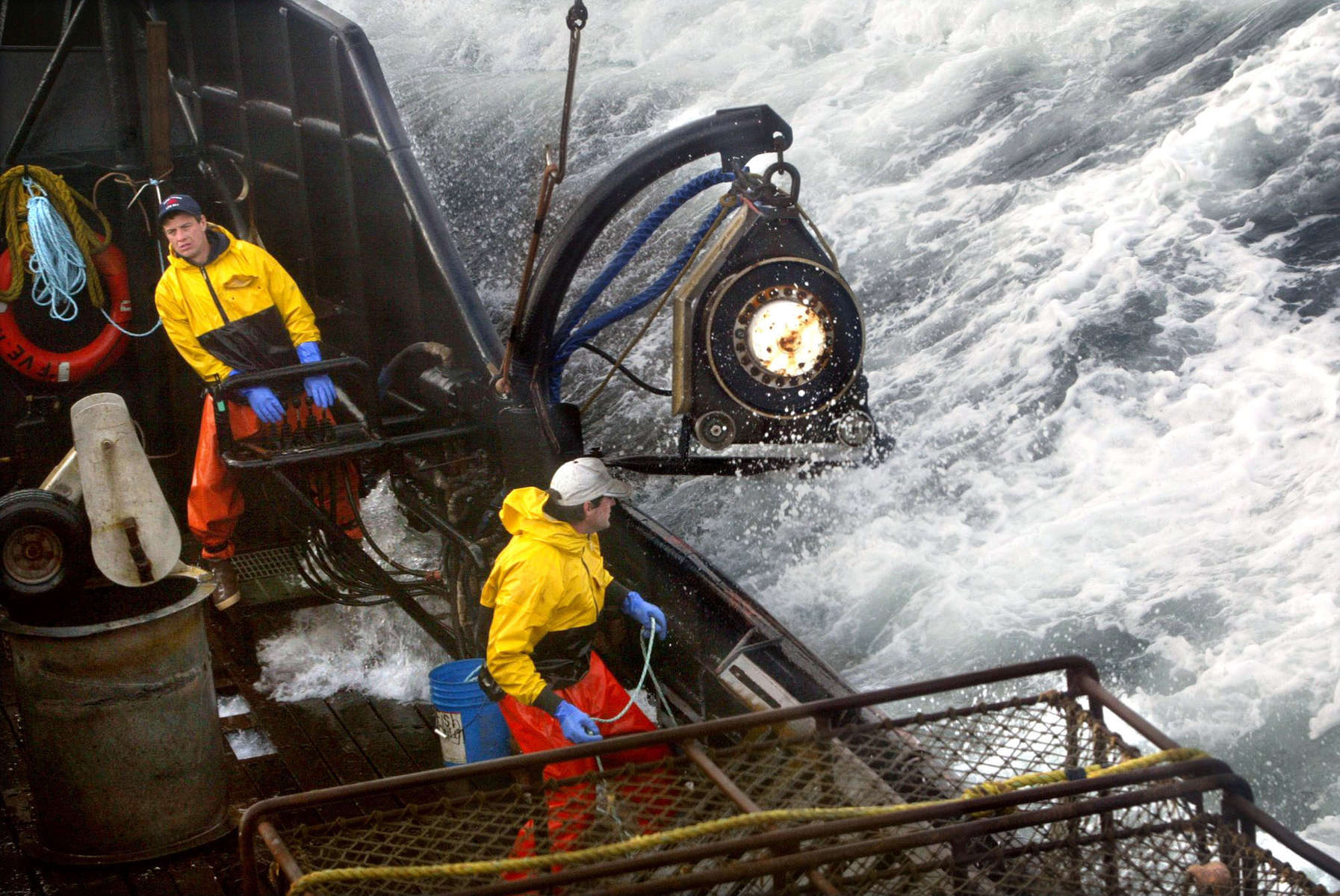 Crewman Lee Fleury prepares to throw the grappling hook at a crab pot buoy off in the distance while Lyndon Yockey (rear) runs the hydrolics to manuever heavy crab pots being stacked onboard. The 20003 Bristol Bay red king crab season lasted 5 days and 2 hours and was plagued with gale force winds of 35 knots or higher almost everyday causing to seas to rise 10 to 15 feet. (© copyright Karen Ducey)