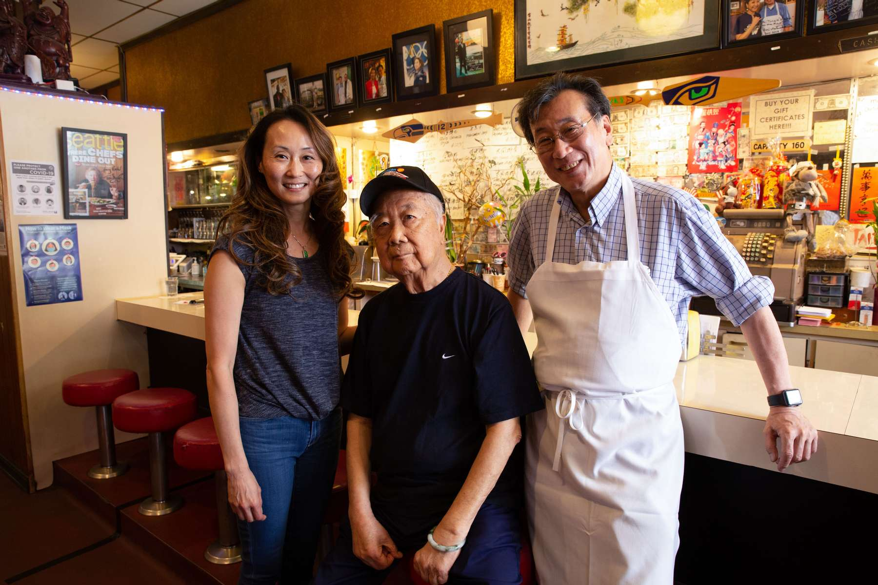 Harry Chan, his brother Tommy Quan and daughter Lisa Chan at the Tai Tung Restaurant in the Chinatown–International District in Seattle, Washington on July 20, 2020. Chan's restaurant was broken into three nights in a row last week. The Chan family has owned the restaurant since 1935.(photo by Karen Ducey)
