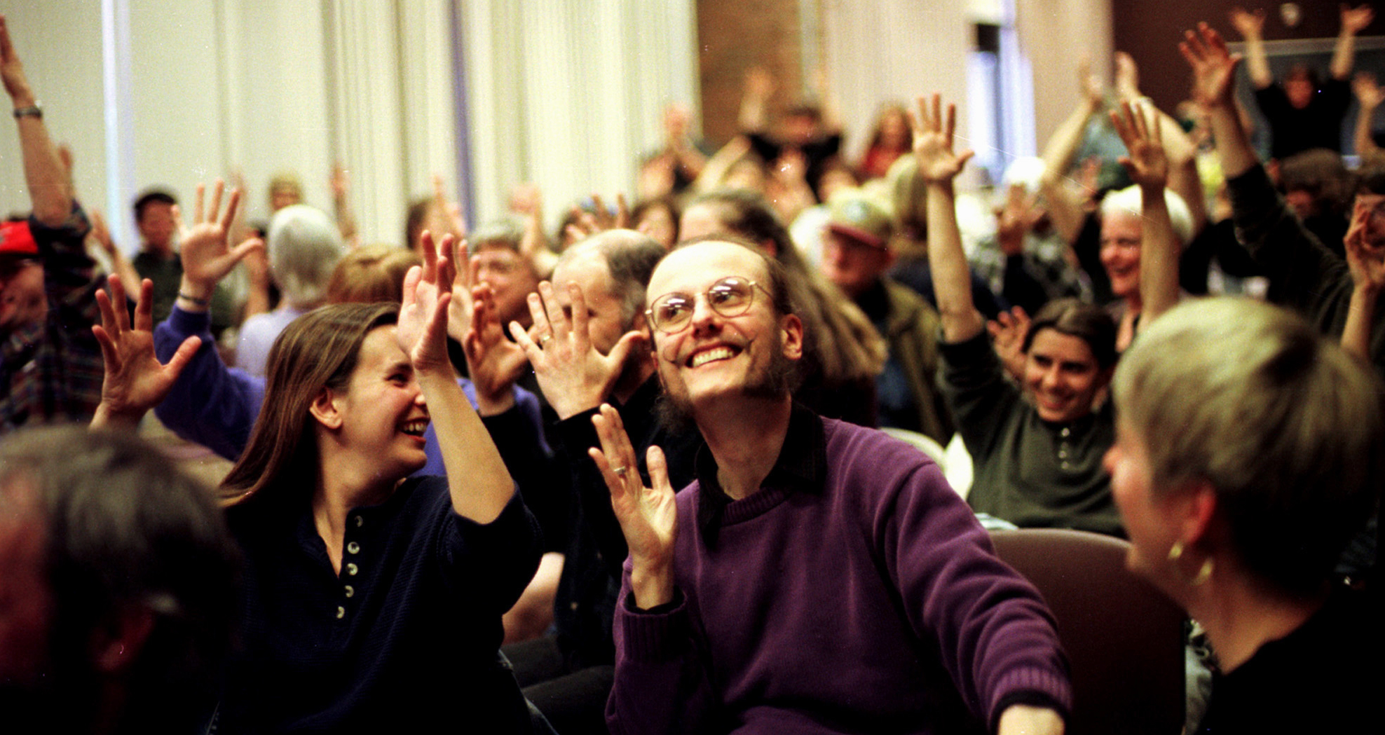 Robert J. Steppler (center) who is deaf-blind joins other people and their interpreters in applause at one of the deaf-blind community classes held biweekly.  In the hearing culture, people clap to give applause. In the deaf culture people wave their hands in the air, and in the deaf-blind culture people wave their hands and stomp their feet to create vibrations.