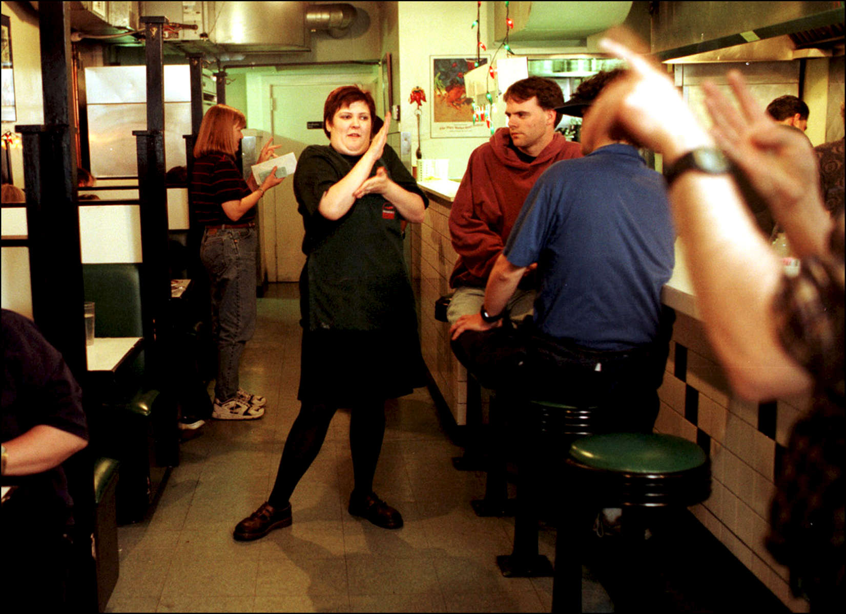 A waitress talks to patrons at the Rajin Cajin, a downtown Seattle restuarant owned by Danny Delcambre who is deaf and legally blind.