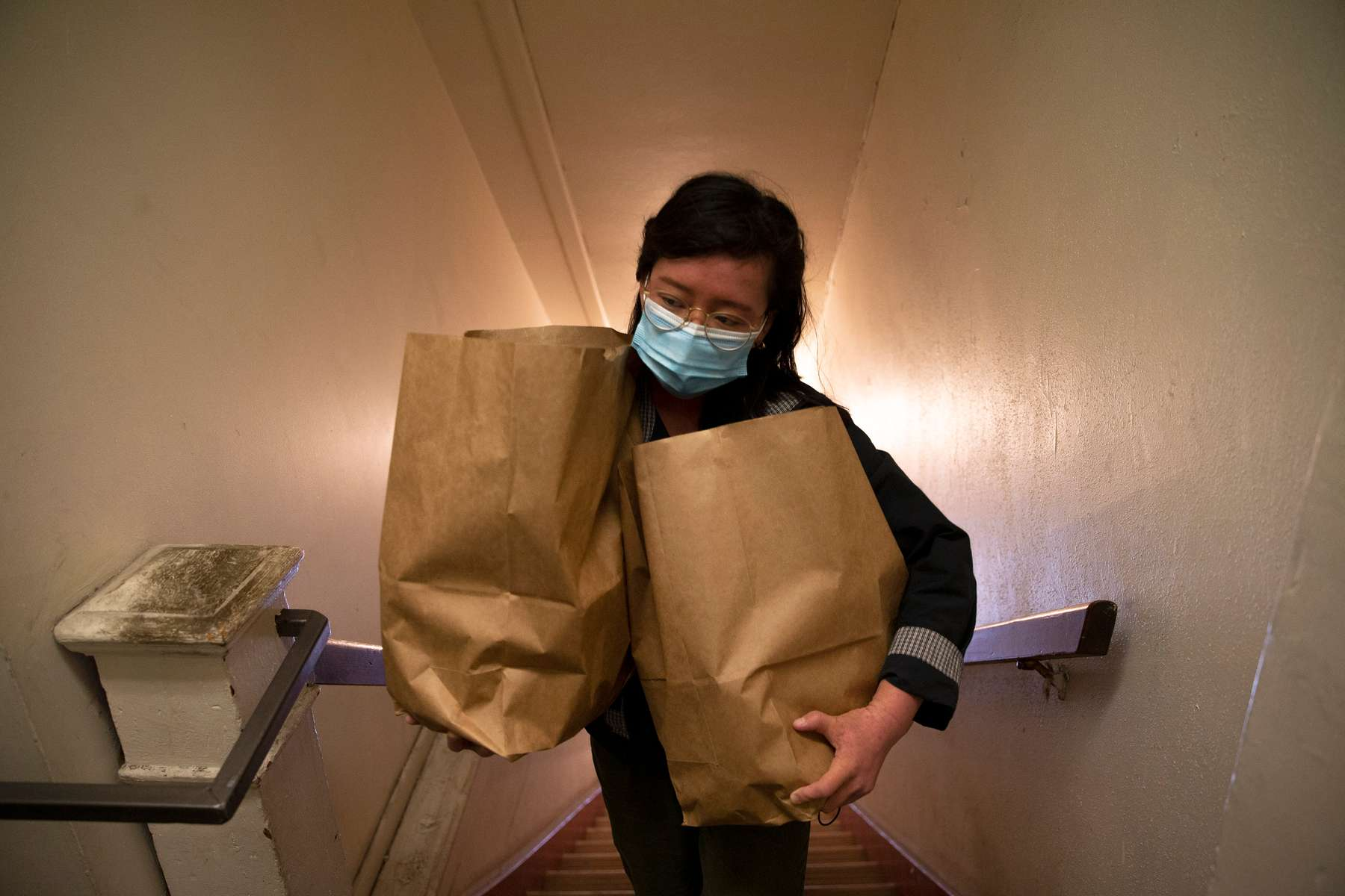 """Volunteer Carmen Hom, from the InterIm Community Development Association, delivers groceries to elderly and low-income residents in the Chinatown-International District in Seattle, Washington on May 28, 2020. Since the coronavirus pandemic began, non-profits in the area banded together to prepare and deliver hot meals and groceries to people afraid to go out because of racial profiling and fear of catching Covid-19. Says Vincent Kwan, the program manager for InterIm, """"It's called disaster gentrification. An already vulnerable neighborhood - having the impacts of COVID is already accelerating the gentrification that's already happening. So, we're very concerned about that."""""""