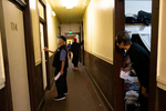 A resident in the Bing Kong Association building, a single room occupancy building, peers out from his door at the commotion in the hallway on April 21, 2020 in the Chinatown-International District in Seattle, WA. An employee from the Seattle Chinatown International District Preservation and Development Authority (SCIDpda) delivers masks to residents with the help from the building manager. Each bag contains three masks that were handmade and donated.