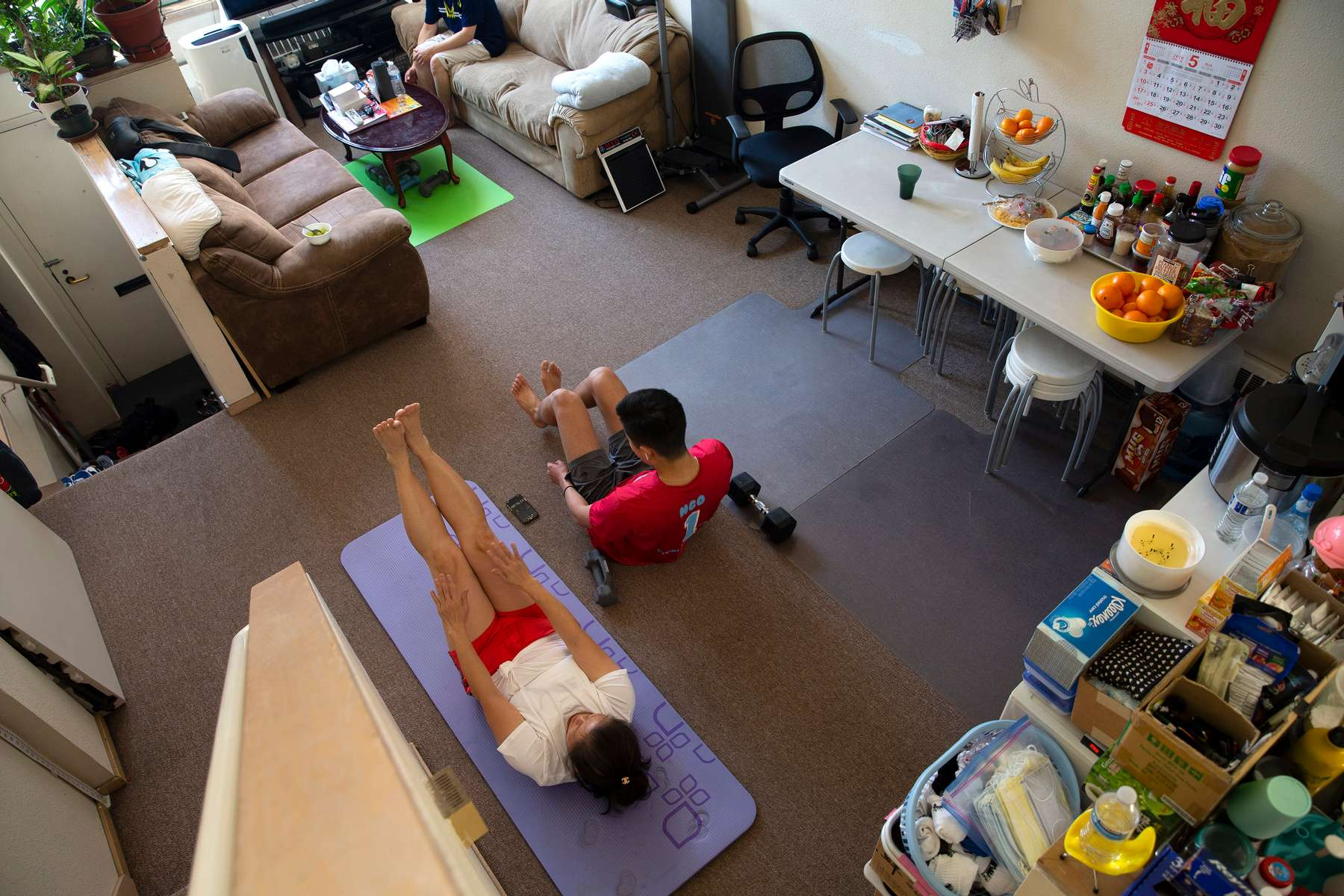 Tony Ngo, 20, a student at Carleton College, works out with his mother in his parents living room in Seattle, Wash. on May 7, 2020.  Ngo moved back in with his parents after his school closed because of the Covid-19 pandemic and said it brought the family closer together. (photo by Karen Ducey)
