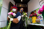 Vicki Hang, 28 and Billy Moua, 25, sell peony flower bouquets from their pop-up stand outside the Kau Kau BBQ restaurant in the Chinatown-International District in Seattle, Washington on June 7, 2020. Normally they would sell the flowers from their families' farm at farmers markets around Seattle but when those closed to curb the spread of Covid-19 the restaurant owner said they could sell them in his underused doorway.