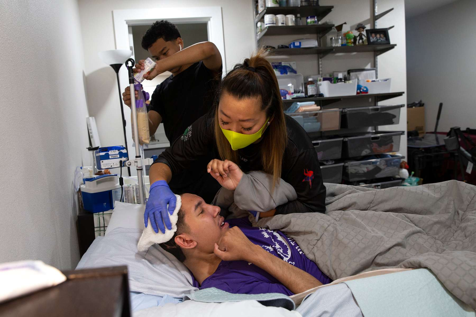 """Dawn Ung cares for her oldest son, Devin, 20, with assistance from her other son, Darin, 17, at their home in Seattle, Wash. on August 10, 2020. Devin was in a car accident several years ago that left him severely disabled from a traumatic brain injury. As a single mother, Dawn has to manage the needs of her three children, as well as, her job at the International Community Health Center, and worries she could bring Covid-19 into their home. """"There's always speed bumps. Nothing really goes as planned in my world, so I just take it as it comes. I think that's the only way I know how to deal with things without making me crazy. I'm surprised I haven't gone insane yet."""""""