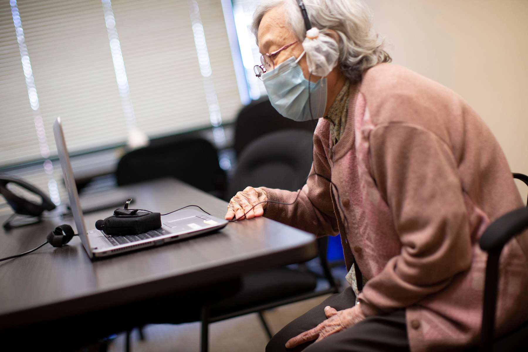 """Wong Wai, 94, a resident at the Legacy House, speaks on a ZOOM meeting with her children and grandchildren in Seattle, WA. on May 29, 2020. Originally from mainland China, Wai does not speak English. The Legacy House set up a laptop so residents could communicate with their loved ones. Says Raymond He from International Community Health Center, who runs the assisted living facility, about the family, """"They're super grateful. I know they're all very concerned, especially with the news that's been going on right now. It's just a lot of scary news. So just seeing that their parents are here, healthy, safe. It's just really enlightening for them."""""""