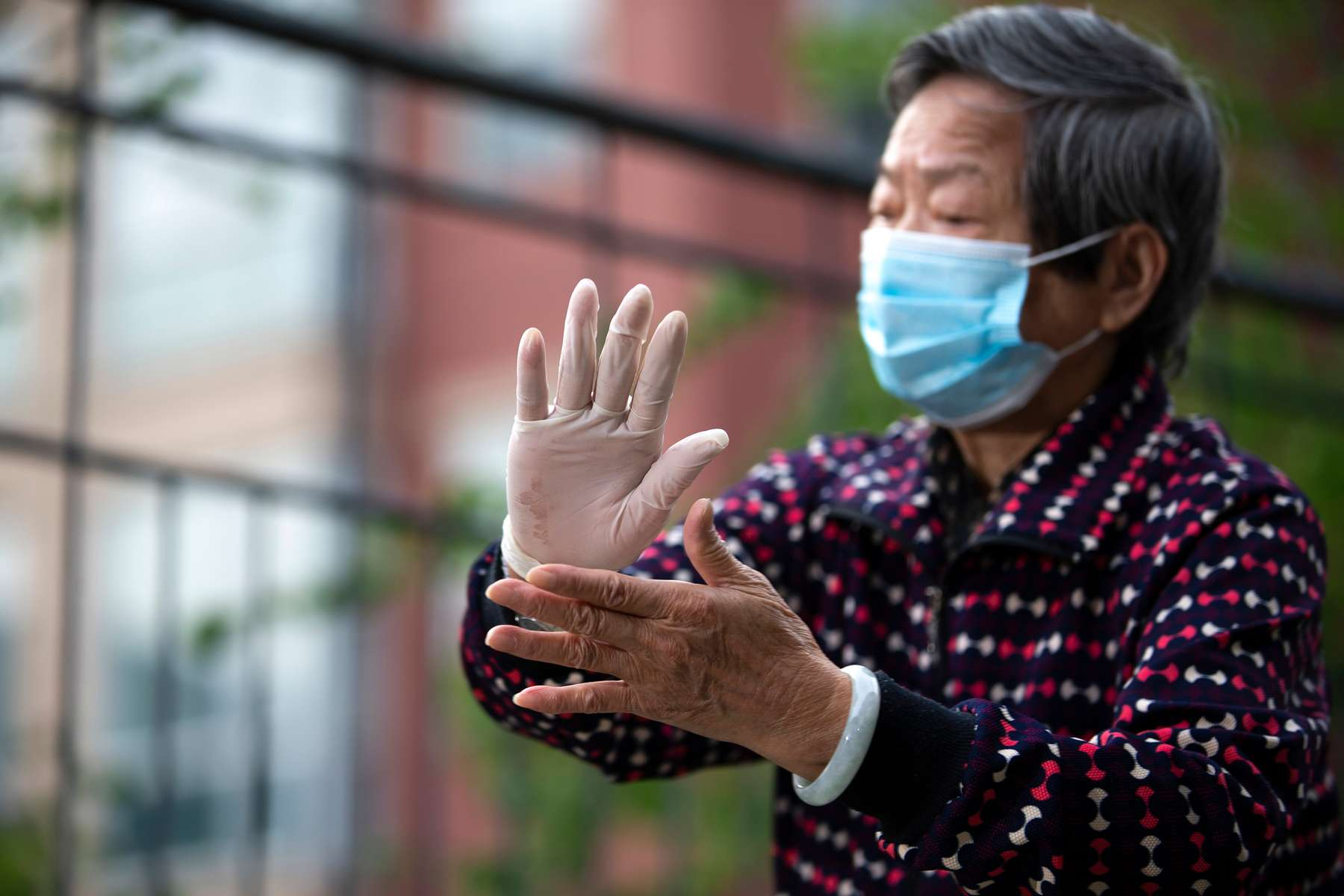 """Tan Zhong Lian, an 86 year-old Chinese immigrant from the Guangdong province, practices Tai Chi on a balcony at the Legacy House on May 26, 2020. Lian normally would do her daily exercise at a nearby park but since the Governor's Stay-at-Home order she has had to practice on the balcony of the assisted living facility. """"Now I cannot go out because I get infected if I go out, so I have to stay inside. So I do exercise in the morning and then evening and I feel satisfied with everything I have…. At the beginning it's so difficult. Just start to quarantine, so difficult. Didn't know what to do. So boring, cannot go out. Now I got used to it because I find a place I can do exercise."""""""