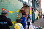 5th graders from Mr. Daichi Hirataís class at the Waldorf School, including Kabir Sethi (center), 11, and Mika Kodama- Chew (on ladder) paint a mural of a Chinese lion over the boarded up storefront of the Fortuna Cafe in Seattle, WA on June 9, 2020. Many storefronts were damaged after a night of rioting swept through the CID after the death of George Floyd, a black man who died when a police officer pinned him to the ground with a knee on his neck. The community responded by boarding up storefronts and hosting artist events to brighten up the streets with murals painted on them. The kids were distracted by firemen putting out a fire at the building across the street. (photo by Karen Ducey)