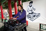 Sheila Locke from NastyMix Entertainment spins some Asian fusion tunes at Hing Hay Park during a community arts event in the Chinatown-International-District in Seattle Washington on June 14, 2020. Dozens of artists came together to paint murals in support of the Black Lives Matter movement on plywood at businesses that had been boarded up because of recent riots and the spread of coronavirus.