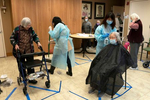 """Employees from the International Community Health Center transform a community room at the Legacy House, an assisted living facility, into a makeshift salon, in Seattle, Wash. on November 12, 2020. """"Today we're providing haircuts for our residents."""" says Raymond He, a supervisor. """"I think this came out of necessity. A lot of the residents, I mean, it's been a while since they've even left the facility and their hair has gotten so long. Family members that have been watching them over video calls or maybe come by to drop off something, they've noticed their hair has been getting too long for them.I think they're very considerate about my lack of skill. They just want it shorter, just easier to manage."""""""