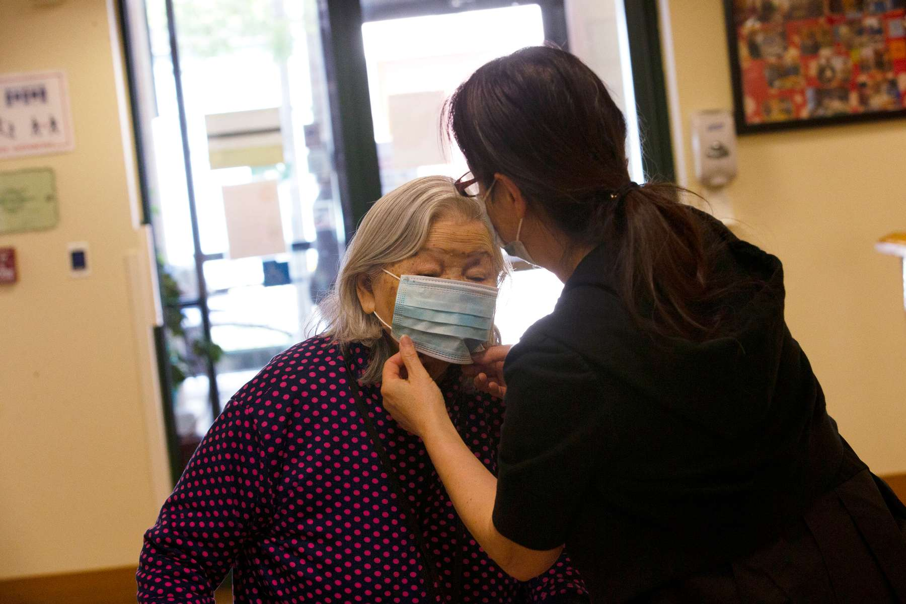 """Sherri Chu, the front desk coordinator at the Legacy House, and assisted living facility associated with the International Community Health Center, fixes a mask on resident Chen Zhixian. """"We try our best to make sure the residents wear a mask,"""" she says in Seattle, Wash. on May 29, 2020."""