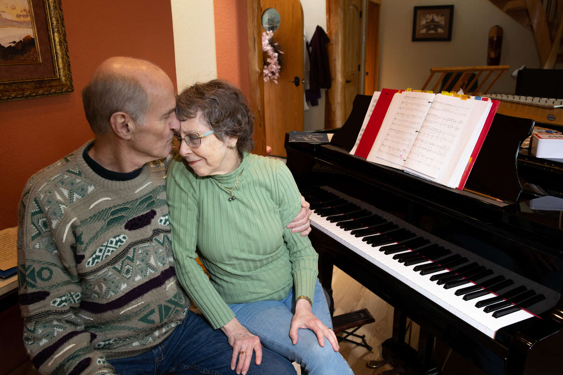 Mark Backlund, 73, gives his wife, Ruth Backlund, 72, a kiss as the two recover from the coronavirus (COVID-19) at their home in Anacortes, Washington on March 27, 2020. Both of them are singers in the Skagit Valley Chorale that experienced a huge uptick in members getting the coronavirus after a rehearsal at a church in Mount Vernon, Washinton on March 10. 27 tested positive for COVID-19. Two have died. The outbreak in a rural community shows how contagious coronavirus is, and how quickly it can spread. (photo by Karen Ducey for the LA Times)