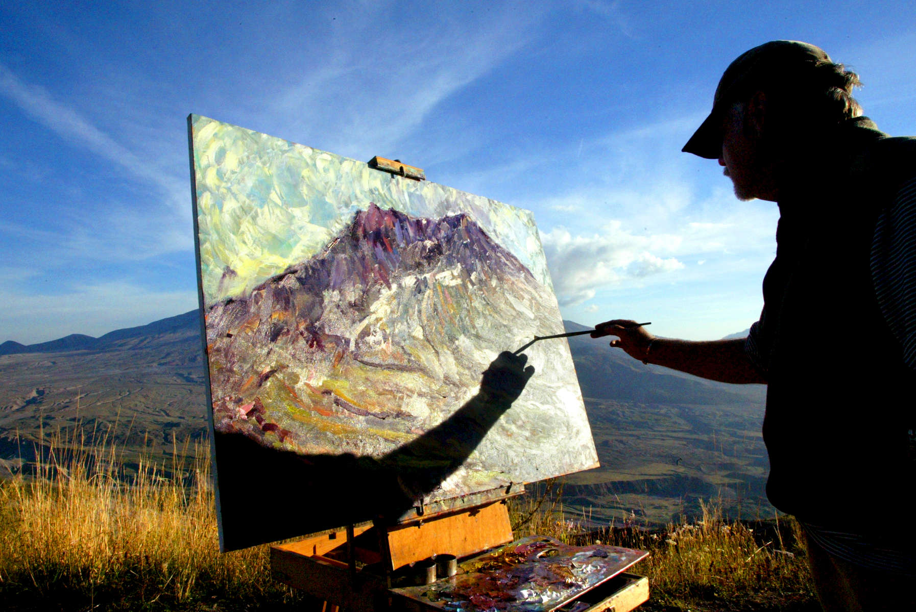 Roderick Smith from Portland, Oregon works on a painting he calls {quote}The Last Tango with Mount St. Helens{quote} outside the Johnston Hill Observatory in Washington on September 30, 2004. Active seismic activity has led scientists to believe the volcano could erupt any day. (© copyright Karen Ducey)