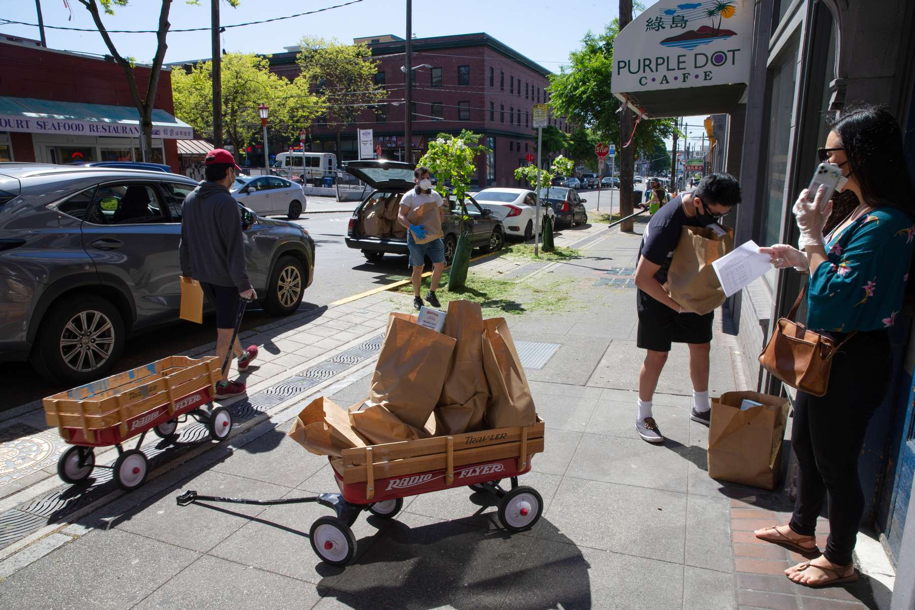 Volunteers and staff distribute food and groceries throughout the Chinatown-International District on May 7, 2020. Vincent Kwan, a program manager at InterIm says{quote}It's called disaster gentrification. An already vulnerable neighborhood having the impacts of COVID is already accelerating the gentrification that's already happening. So, we're very concerned about that.This community is meant for people that have been marginalized, have been pushed away from white neighborhoods historically. And they found refuge here. How do we protect a historical landmark and also a historical place for folks that call it home?{quote}(photo by Karen Ducey)