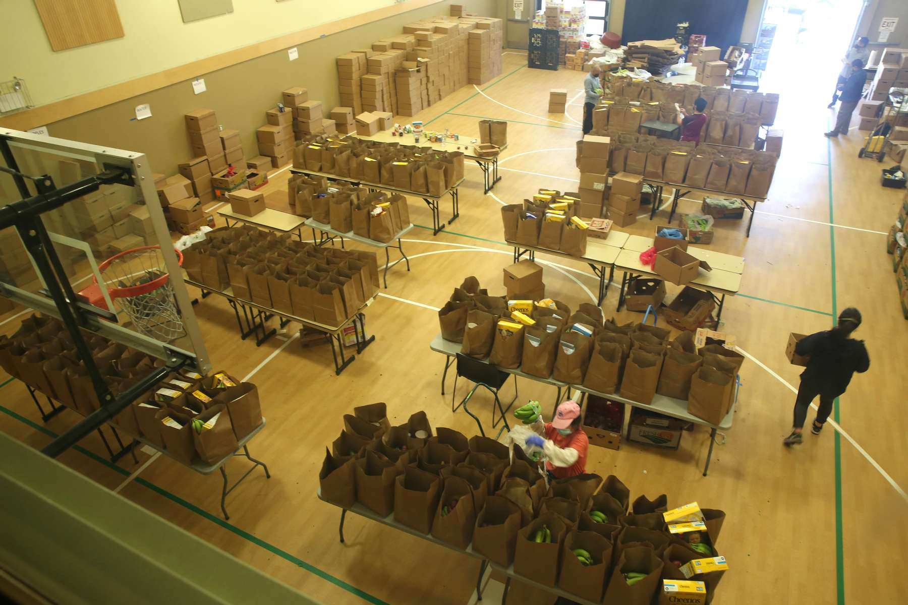 """A gymnasium is transformed into an area where staff and volunteers packed bags of groceries to be distributed to seniors throughout King County at the Asian Counseling and Referral Service in Seattle, Wash. on May 30, 2021. Approximately 2,250 meals and 2,250 grocery bags were prepared each week, delivered Monday through Friday. The vast majority of meals and bagged groceries went to AAPI elders. Many of them live in the CID; however, King County Access Transportation and various community groups help to deliver to isolated and homebound elders all over King County. Volunteer drivers from over 20 organizations delivered the meals. Says Liza Javier, communications manager at ACRS, """"We wanted to provide healthy meals and groceries to elders during the pandemic while ensuring they could remain safe at home."""" (photos by Karen Ducey)"""