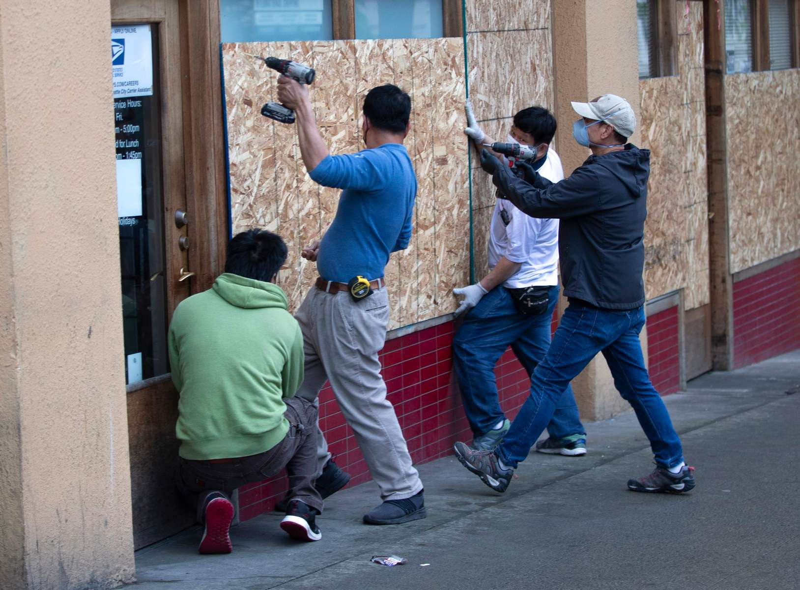 Maintenance crews from SCIDpda board up storefronts on one their buildings on Jackson St. after a night of protests in the Chinatown-International District in Seattle, Wash. on May 30, 2020. Protests around the country became violent over the past couple days after the police killing of George Floyd, a black man in Minneapolis. (photo by Karen Ducey)