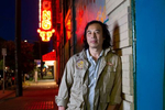 """Johnny Chan photographed in the Chinatown–International District in Seattle, Washington on July 15, 2020. Behind him is a photo of Donnie Chin on their bordered up storefront. Chan was one of """"Donnie's Kids"""" when he grew up in the neighborhood in the 80's and spent a lot time and late nights working with Donnie to protect the neighborhood. Donnie Chin, director of the International District Emergency Center (IDEC) was murdered on July 23, 2015. The murderer was never found. (Photo by Karen Ducey) (Photo by Karen Ducey)"""