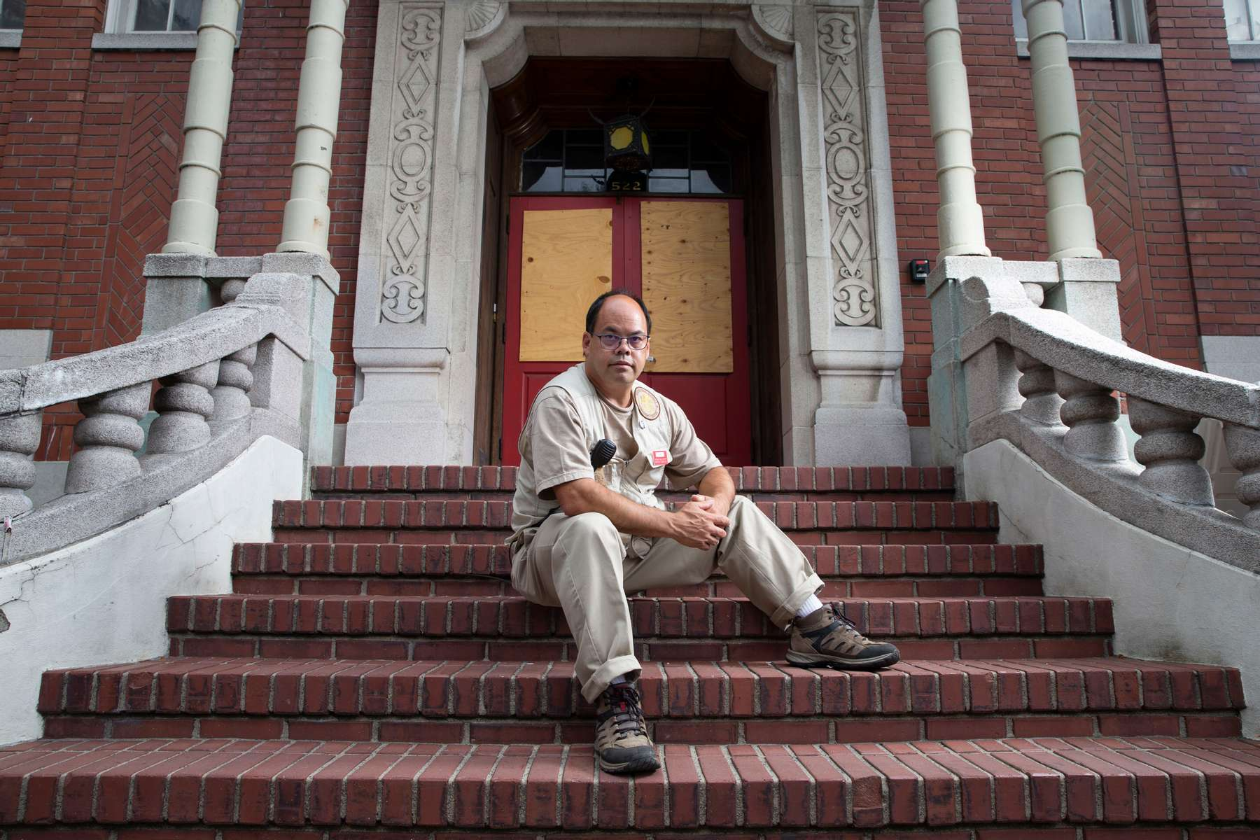 """Kay Chinn sits on the front steps of the Chong Wa Benevolent Association in the Chinatown - International District in Seattle, Washington on July 17, 2020. Kay was one of """"Donnie's Kids"""" as he grew up in the neighborhood in the 80's and participated in programs started by Donnie Chin, director of the International District Emergency Center (IDEC). At one time the  building housed the Chinese School. (Photo by Karen Ducey)"""