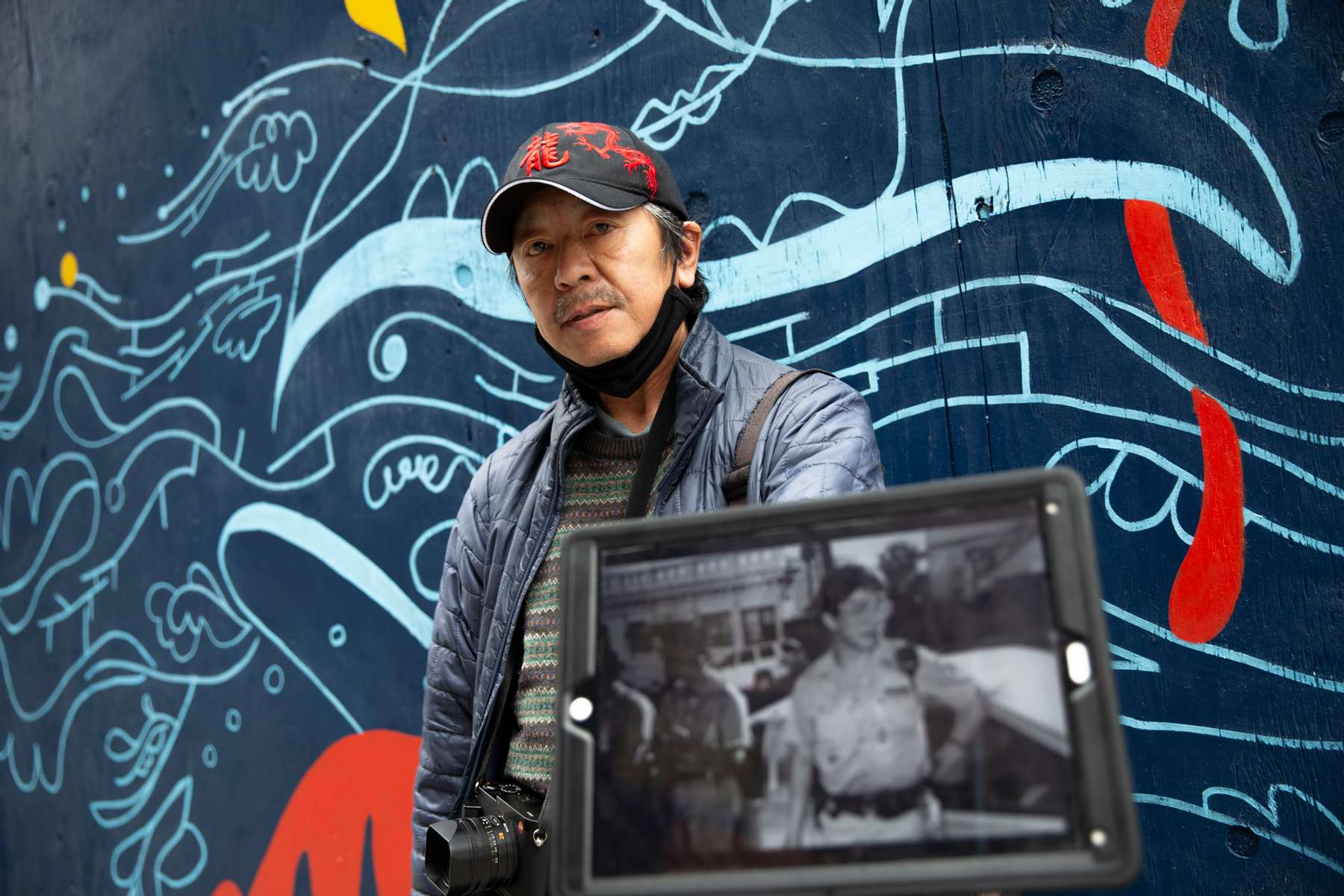 """Photographer and co-founder of the International District Emergency Center (IDEC), Dean Wong, holdsa picture of Donnie Chin many years ago in the Chinatown - International District in Seattle, Washington on July 16 and 17, 2020. """"He was Dragon one. I was Dragon two,"""" says Wong explaining that all the volunteers had a code name on the radio. Donnie Chin, director of the International District Emergency Center (IDEC) was murdered on July 23, 2015. The murderer was never found. The mural behind him was painted by Moses Sun and the Wing Luke Museum staff on the boards protecting the windows after the riots from the Black Lives Matter movement. (Photo by Karen Ducey)"""