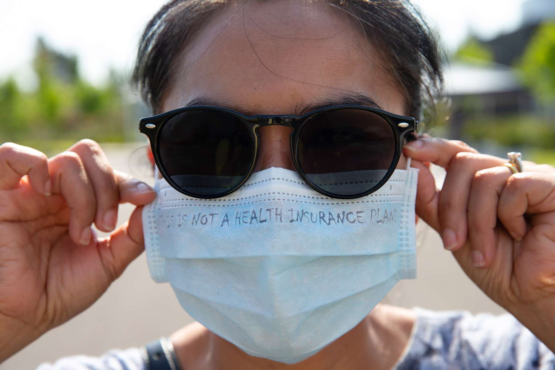 Rattana Chaokhote, Clinical Services supervisor at ICHS dons a mask that reads, {quote}This is not a health insurance plan,{quote} at a COVID-19 drive thru and walk-in testing site held for people in the Pacific Islander community in collaboration with International Community Health Services at Federal Way High School Federal Way, Washington on July 31, 2020. A recent report by the Washington State Department of Health (DOH) and Bellevue-based Institute for Disease Modeling (IDM) analyzing COVID-19 data highlight the pandemicís disproportionate and increasing impact on communities of color. Case rates over the pandemic for Hispanic people and Native Hawaiian or Other Pacific Islander people are nine times higher than those of White people. Hospitalization rates are seven times higher for Hispanics and ten times higher for Native Hawaiians or other Pacific Islanders than those of White people. ìWe know the COVID-19 pandemic has intensified the health inequities historically marginalized and oppressed communities already experience,î said Dr. Kathy Lofy, state health officer at DOH. ìThese data are deeply concerning and underline the critical need to address the COVID-19 impacts weíre currently seeing by prioritizing outreach, testing, education and related materials for disproportionately impacted communities in ways that are culturally and linguistically appropriate and accessible.