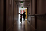 """Sabrina, age 4, and Smira Sanura, age 6, run through the hallway of the Mercy House as their family remains in quarantine to help curb the spread of Covid-19 in Seattle, Wash. on October 21, 2020. They live with three other siblings including a newborn, two parents who work, and their grandmother in their apartment. One of the girls says the hardest thing about online learning is you have to mute and unmute yourself. She says this year has been difficult because sometimes other kids are allowed outside to play but their mother won't let them. ICHS has a partnership with the Mercy House to pilot onsite health and wellness classes and events there. The girl's mother, Amina Osman who works as a nurse says, """"The biggest challenge is the fact that you have to be a mom and be a teacher at the same time. You have to multitask. Make sure food is at home and everything. So it's, it's been a tough taking care of a newborn and managing the kids as well.{quote} (photo by Karen Ducey)"""