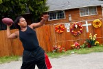 Jordan plays football in the street in front of his house where a memorial to his brother still stands. He dreams of being a football player someday.    © Karen Ducey/ Seattle PI