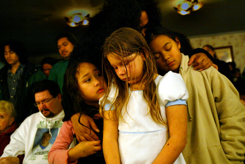 "Hugged by their mother, siblings mourn their older brother's death at a holiday service at the Greenwood Memorial Park Cemetery in Renton, Wash. on Sunday, December 10, 2006.  Their older brother, Michael Miller, had been killed several months ago after he was accidentally shot by another teenage brother while the two were playing with a handgun in the family's home.  ""I really miss him,"" says Mataio Jantoc, 10 (right).  ""Even though we're little, this has had one of the biggest impacts in our life and it just really hurts.""  From left to right: Tim Miller, father, Merina Sanchez, 5, Brittany Walker, 8, and Mataio Jantoc, 10. They are hugged by their mother, Lena Jantoc, from behind. (© Karen Ducey/ Seattle PI)"