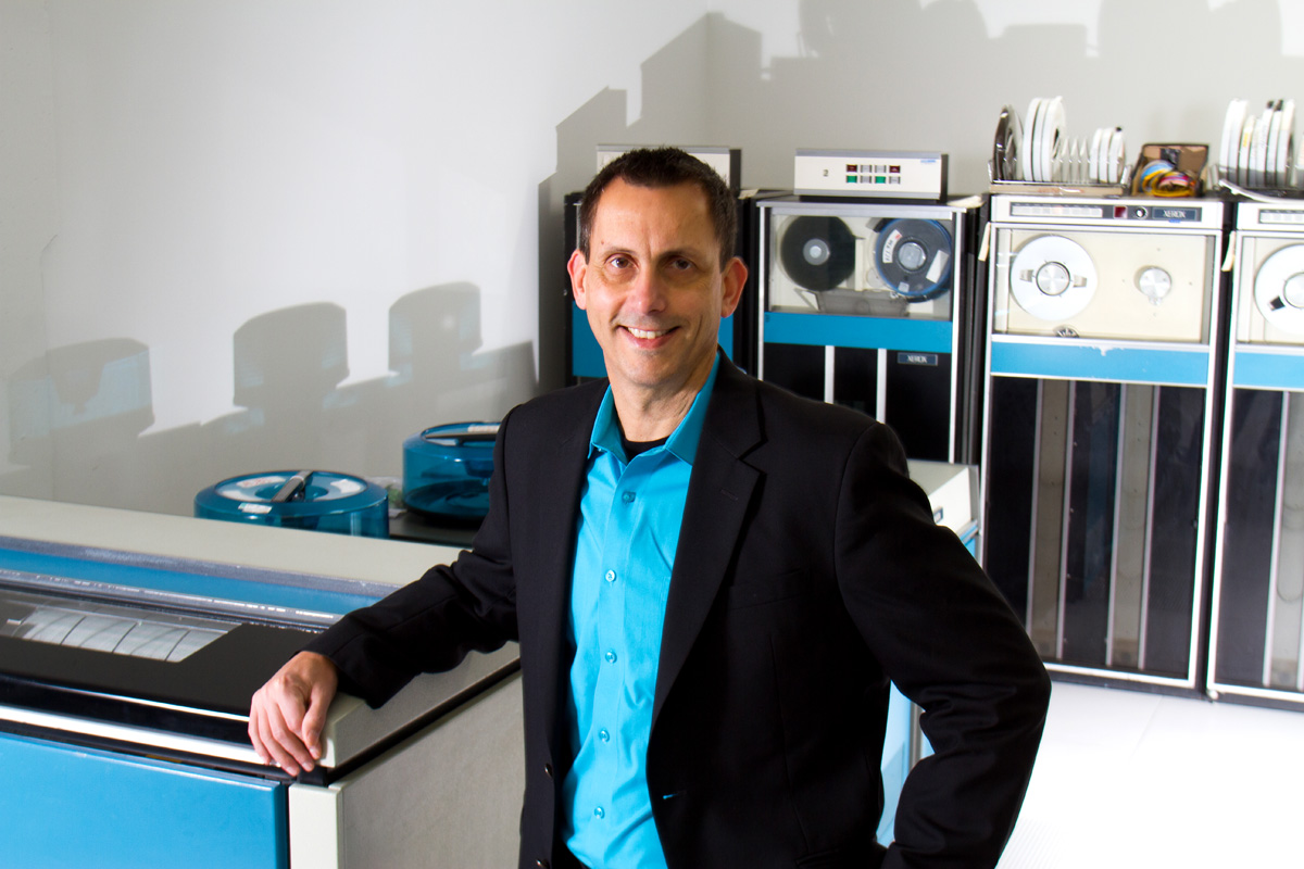 Senior Vice President and Chief Information Officer of Seattle Children's Hospital, Wes Wright, is photographed next to a Sigma 9 Mainframe printer at the Living Computer Museum in Seattle, Washington.  The Sigma 9 tape drives are in the background. (© copyright Karen Ducey)