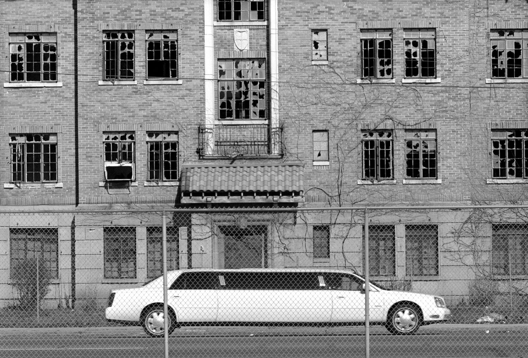 A limousine in town for the Miss USA Beauty Pageant passes by one of Gary's many dilapidated buildings.  In an effort to improve the city 253 buildings were demolished last year. {quote}The city may not have been ready{quote} explains Richard Grey, managing editor of the local paper the Post-Tribune, {quote}but if you wait until you're ready you're never gonna have these things.{quote}  (© Karen Ducey 2001)