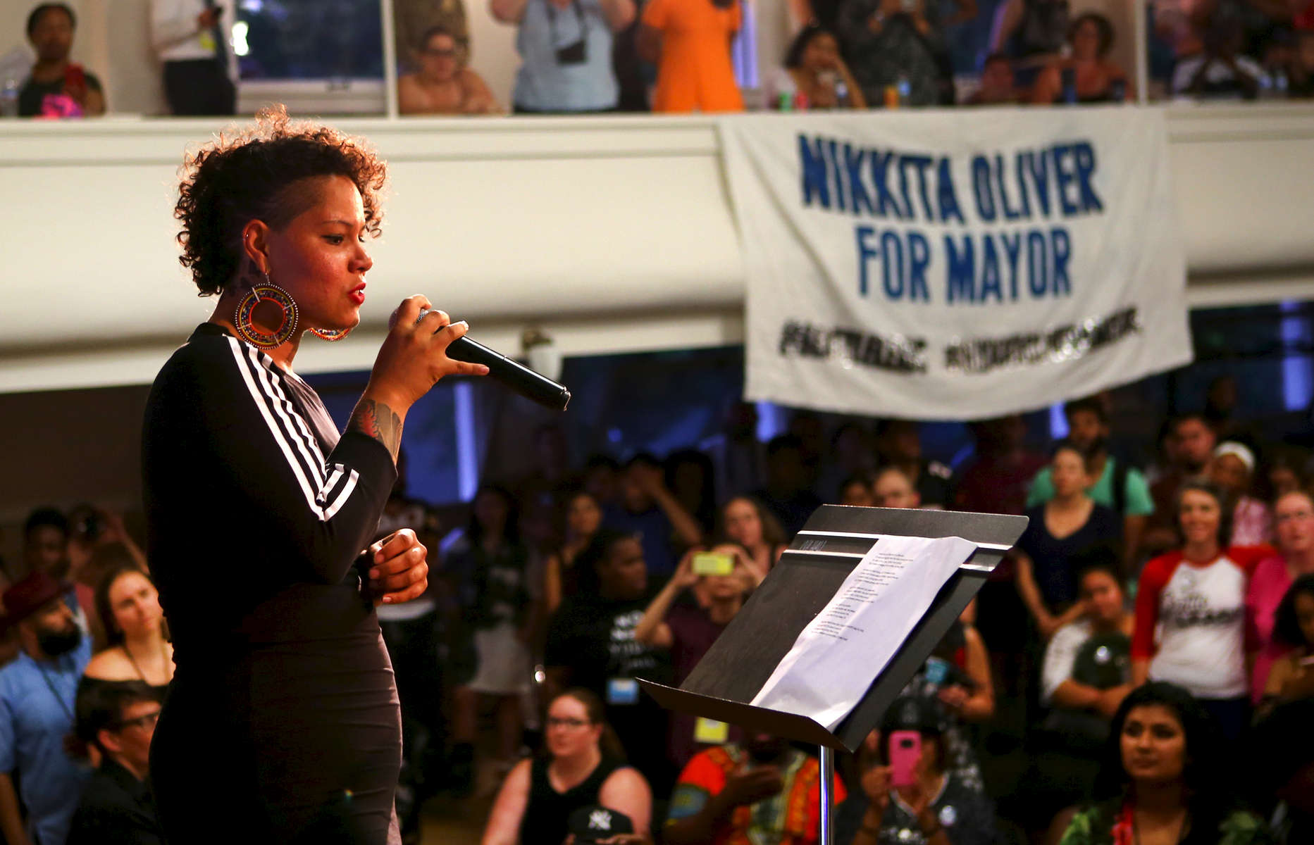 Nikkita Oliver, mayoral candidate of the People's Party of Seattle, speaks to hundreds during a rally for her on primary election night at Washington Hall in Seattle, Wash. on August 1, 2017. (© Karen Ducey)