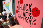 Misha Zadeh and Ben Graham (not in photo) paint a Black Lives Matter mural on the boarded up ICHS Vision Clinic in Seattleís Chinatown International District in Seattle Washington on June 14, 2020. Says Zadeh, {quote}Its really cool to see the arts community come together and put effort into such a good cause.{quote} Several community arts events were held to beautify the boarded up storefronts and support the Black Lives Matter movement. (Photo by Karen Ducey)