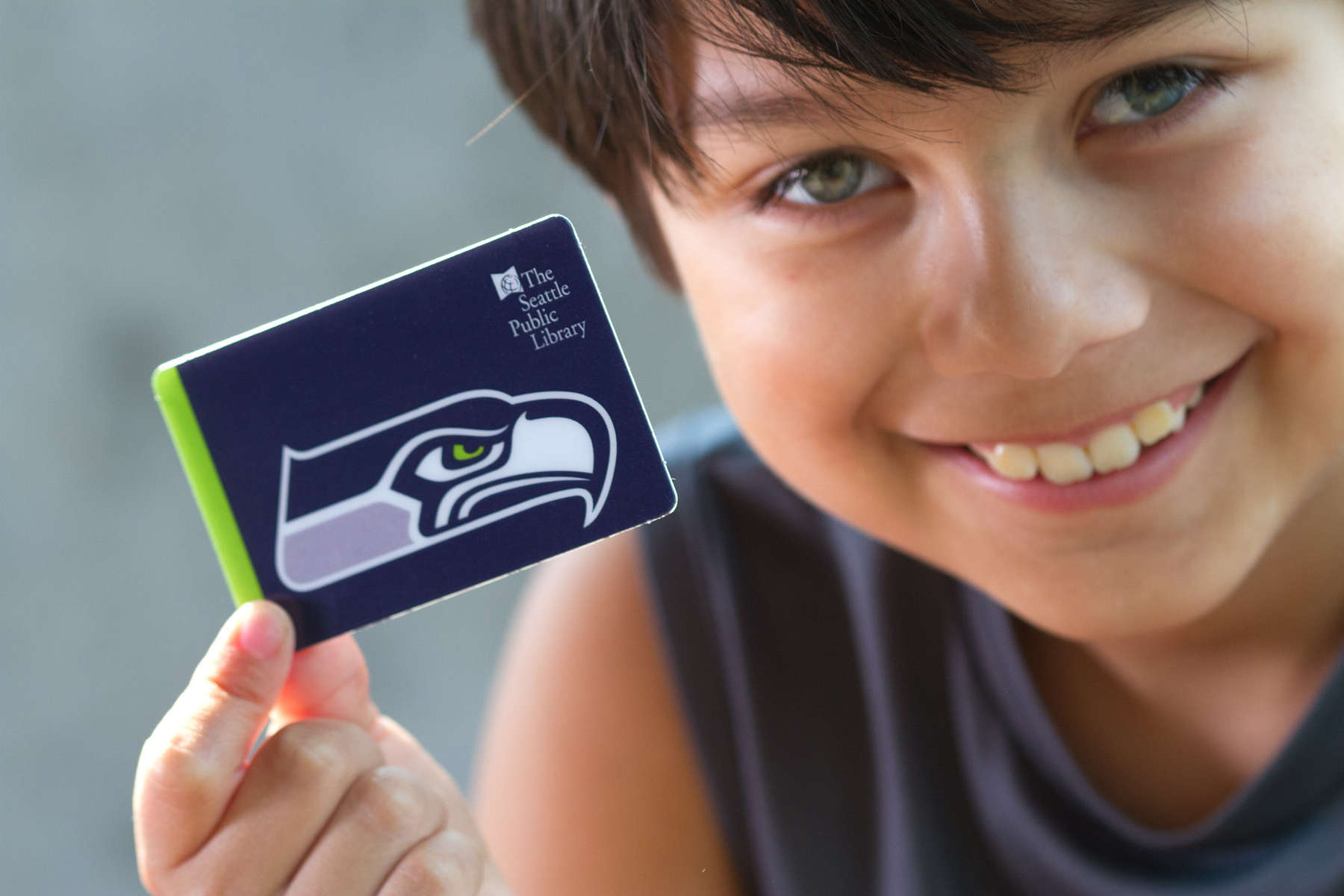 A child holds a Seattle Public Library card with a Seahawks logo on it at the Northgate Library in Seattle, Wash. on August 12, 2015. (photo © Karen Ducey)