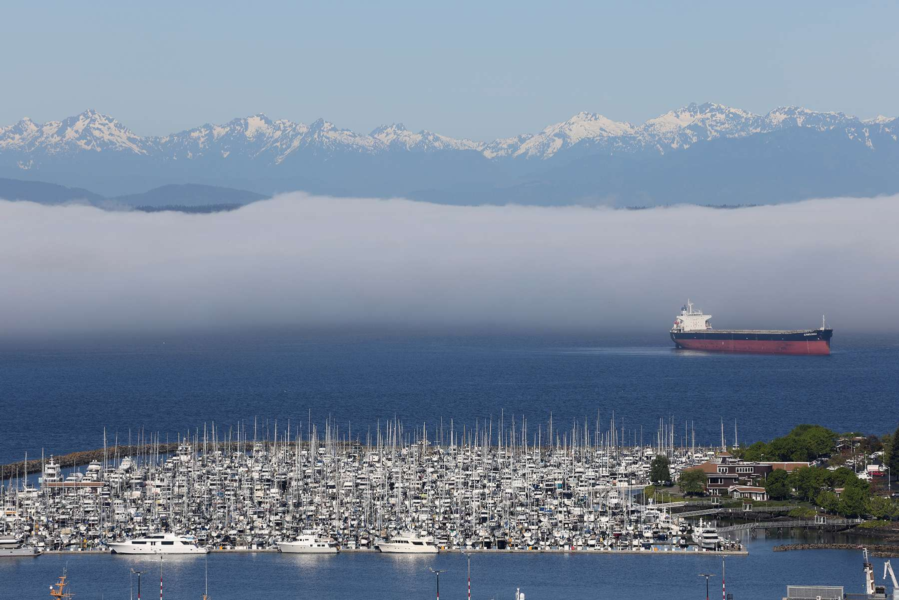 Puget Sound Ship - Weather Permitting photographed for Reuters, photo and interview published on Accuweather.com on May 28, 2021. Low fog sits behind a cargo ship and boat marina and is  framed by the Olympic Mountains visible from the Queen Anne neighborhood of Seattle, Washington, U.S. May 14, 2021.   REUTERS/Karen Ducey