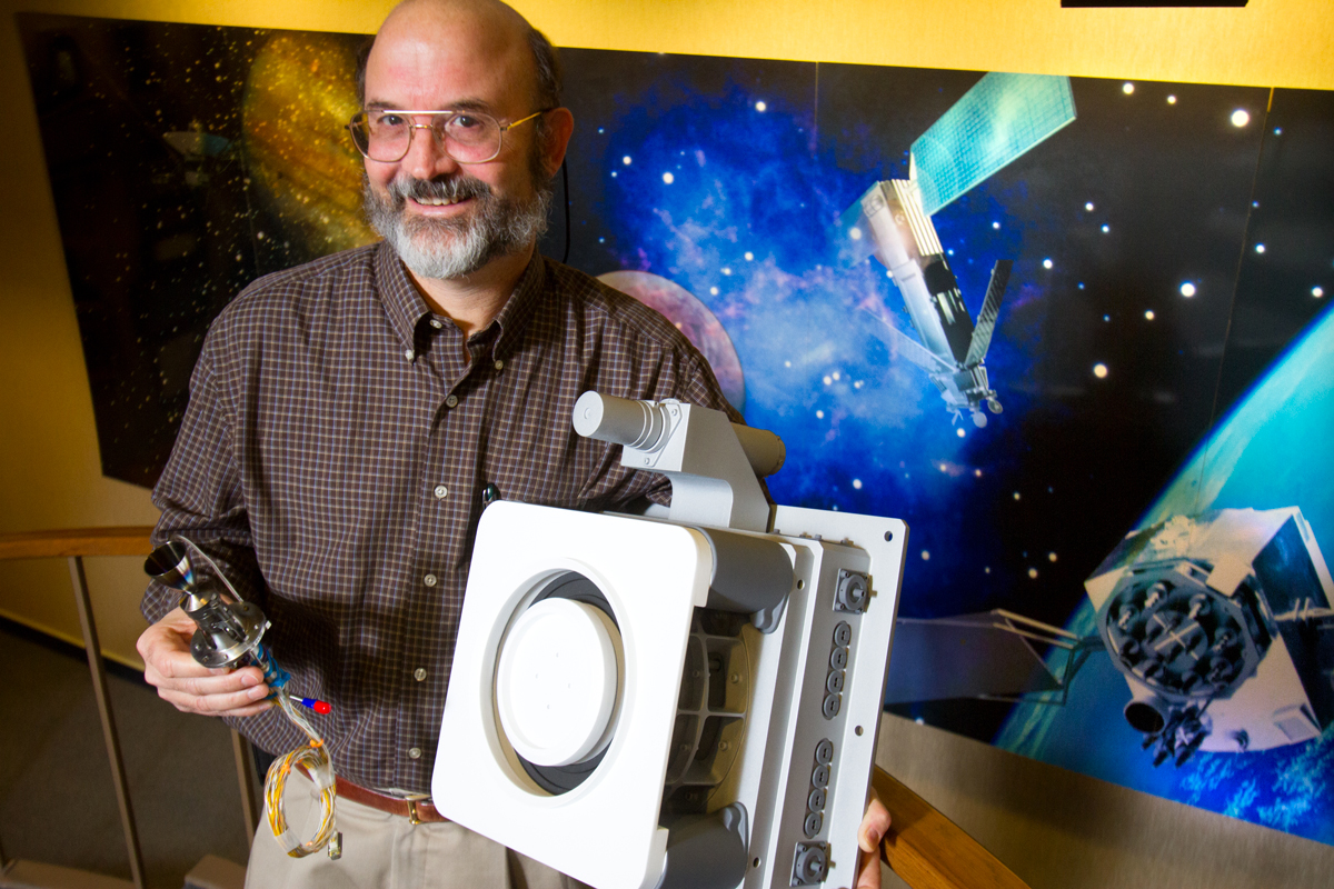 Roger Myers, Executive Director of advanced in-space programs at Aerojet, holds models of a Cygnus MR-107, a chemical thruster (left) and a 12kz XR-12 ion engine thruster for a future Mars mission (right) at the company headquarters in Redmond, WA. Aerojet is the oldest and most established of the local companies working in outer space. The Redmond company makes small rocket motors, most of them used to position satellites in outer space, or to guide long-distance exploration missions. (© copyright Karen Ducey)