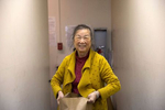 71-year-old Yan Nong Cui receives a bag of groceries delivered by volunteers from InterIm Community Development Association (InterIm CDA), to her home in the Kong Yick building on May 28, 2020. Since the coronavirus pandemic InterIm along with a COVID-19 task force made up of many non-profit organizations in the Asian American community including ICHS have been distributing free groceries and meals to people who have been afraid to go out because of racial profiling, as well as, fears of catching the coronavirus. There is no access to the internet in her building so she must get all news from her phone. (photo by Karen Ducey)