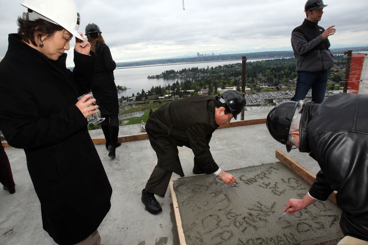 Heidi Lee (left) watches her husband Kenny Lee scribble a name in concrete mix during a ceremony celebrating the freshly poured 43rd story of the eco-luxury Bellevue Towers on May 14, 2008. The Lee's bought a unit on the 12th floor. A bucket of concrete mix (in photo) was brought in by a crane for a ceremonial {quote}final Pour{quote}.  Construction is scheduled to be completed in Novemeber 2008 making it the tallest peak in Bellevue. Thanks in part to the elevated grade of the building site, Bellevue Towers is now the cityís tallest peak.  (© copyright Karen Ducey)