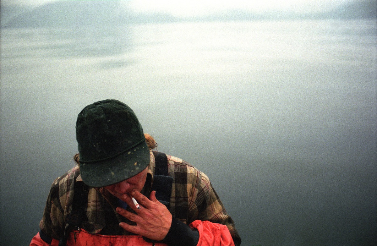 Wanda Bryant smokes a cigarette while halibut fishing in Alaska. (© copyright Karen Ducey)