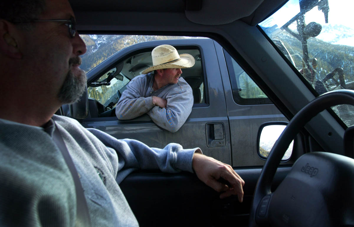 Evan Fink, lead tech from the Washington state Department of Transportation, from Twisp, WA, leans out of his car window to watch a plow shovel snow as he talks with Jeff Adamson (left), DOT communications manager for NW region. (© copyright Karen Ducey)