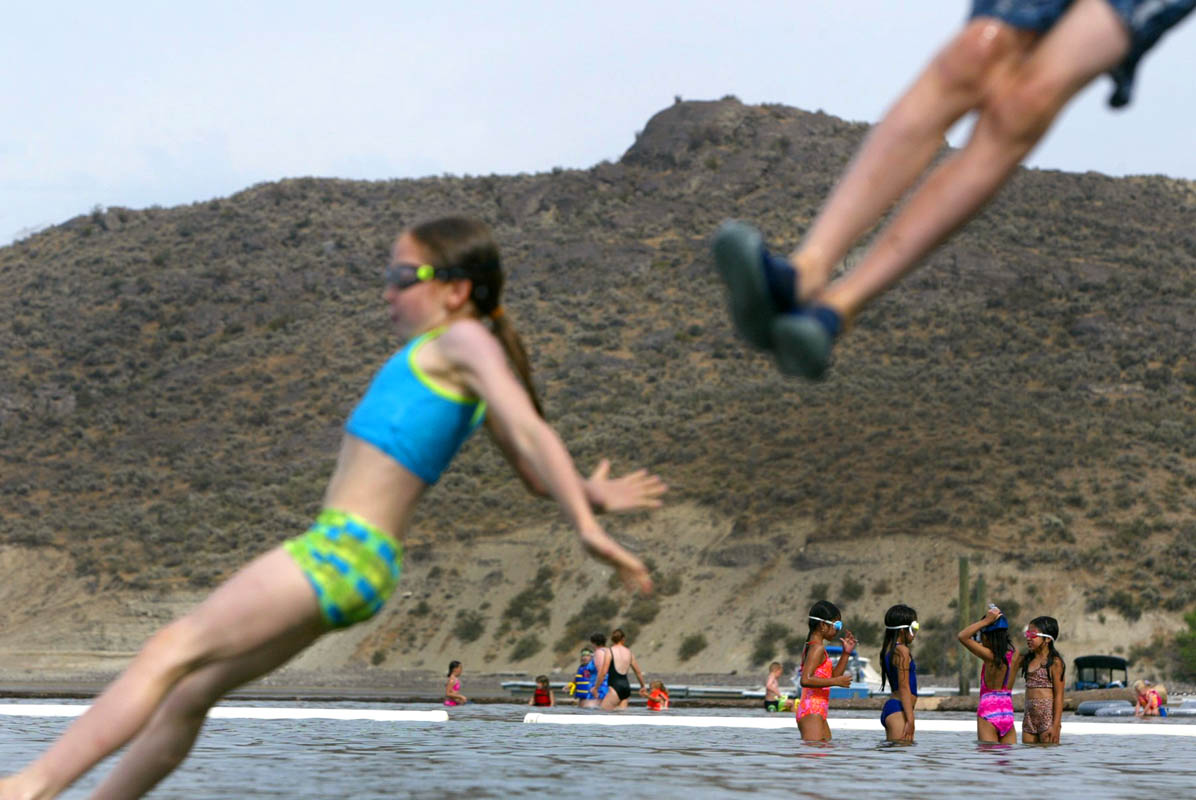 Mackenzie Forman,9 (left) and her brother Chance Forman,8, (feet only) jump into the Franklin D. Roosevelt Lake at Spring Canyon. (© copyright Karen Ducey)