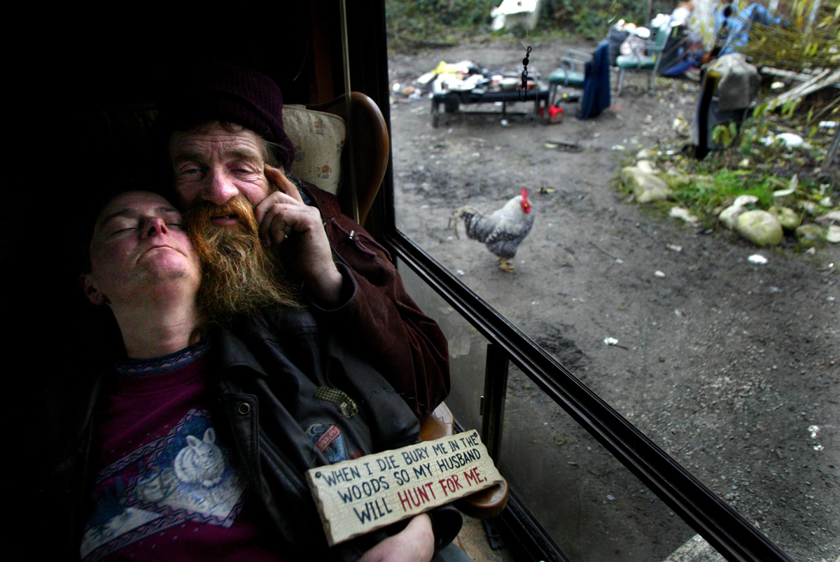 Paula Jean Stierns (left) lies passed out on her husband's lap.  She had lived in a shack with her husband Donald Raymond Stierns (right) for almost four years off N. Skyview Dr. in Sultan,WA. After their shack caught on fire the pair moved into a trailer which someone had donated to them.  About a dozen people live in makeshift housing on the Skyview Dr. upsetting many in the city.  (© copyright Karen Ducey)