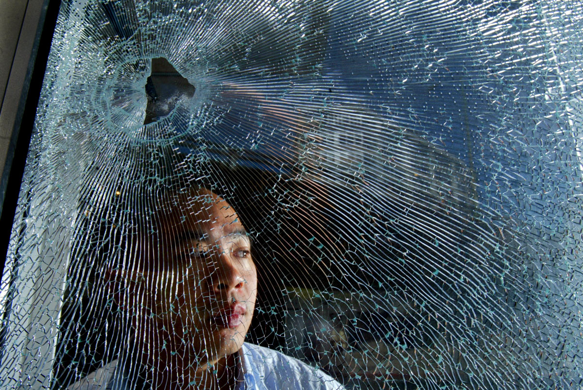 A store owner is concerned with all the gun violence erupting in the neighborhood, including a bullet shot through his window. (© copyright Karen Ducey)