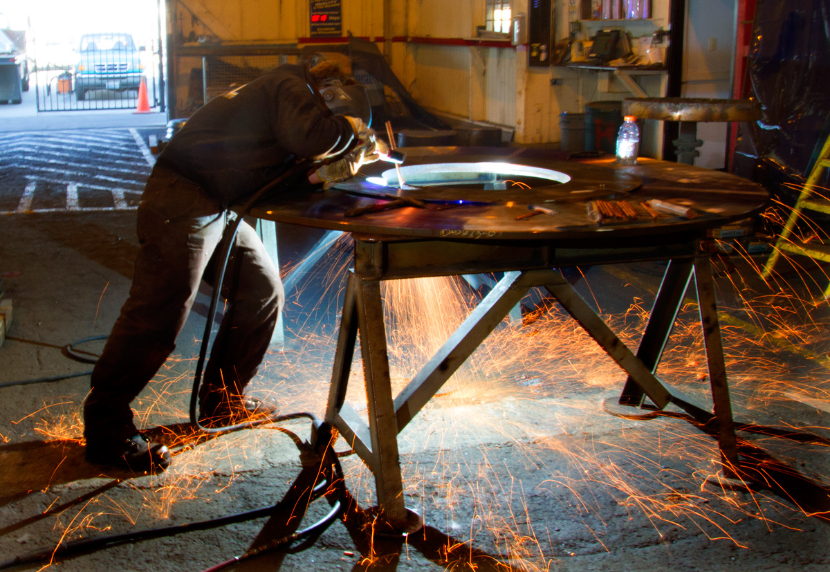Victor Beal, welder and fitter with Markey Machinery, works on a steel drum meant for a work boat.  Beal has been a welder for six years following in the footsteps of his father. Under the new law in Seattle Beal will receive sick leave in addition to his PTO. (© copyright Karen Ducey)