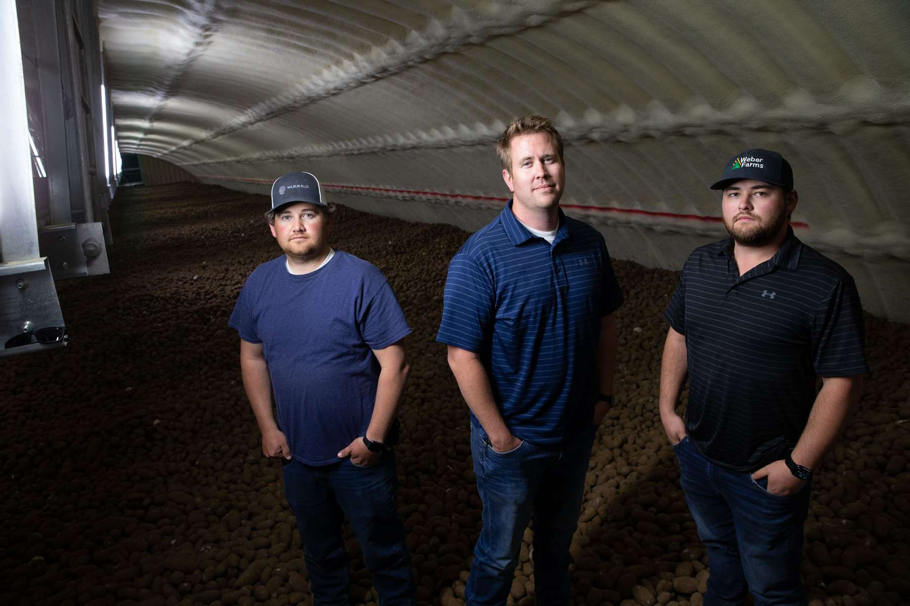 From left to right: Weber Family Farmsí managers and family members, Deven Johnson, Josh Lyebert, and Adam Weber stand on $1.1 million worth of ready-to-eat russet potatoes in one of their refrigerated potato storage bays in Quincy, Washington on May 1, 2020. That particular bay holds 16 million pounds of potatoes, 20 feet deep in a building 340 feet long -just slightly less than the length of a football field. Weber Family Farms is a a third-generation farming family, started by Adam's grandfather, Bill Weber, in the late 1960s.A billion pounds of excess potatoes in Washington state, second largest potato producer in the country. About 70 percent of its crop usually goes to overseas, to Pacific Rim countries primarily, in the form of french fries, but with so many restaurants/food service closed in U.S. and internationally, they have way more potatoes than they can sell. Last year they didnít have enough to meet demand; now growers are facing the prospect of losing it all. (photo by Karen Ducey)