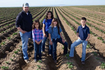 From left to right: Jordan Reed (left and his wife Mia (center) pose for a photo with their children Breanna (left), 5 years,  Addison, 8, and Owen (right), 10 pose in a neighborís potato field in Pasco, Washington on May 1, 2020. Reed, a relatively new farmer had received contracts from processors. He then borrowed $1.7 million to plant 465 acres of Ranger russet potatoes. Since the coronavirus outbreak and the lack of demand for french fries, processors terminated his contracts and he faces the prospect of losing the farm. (photo by Karen Ducey)