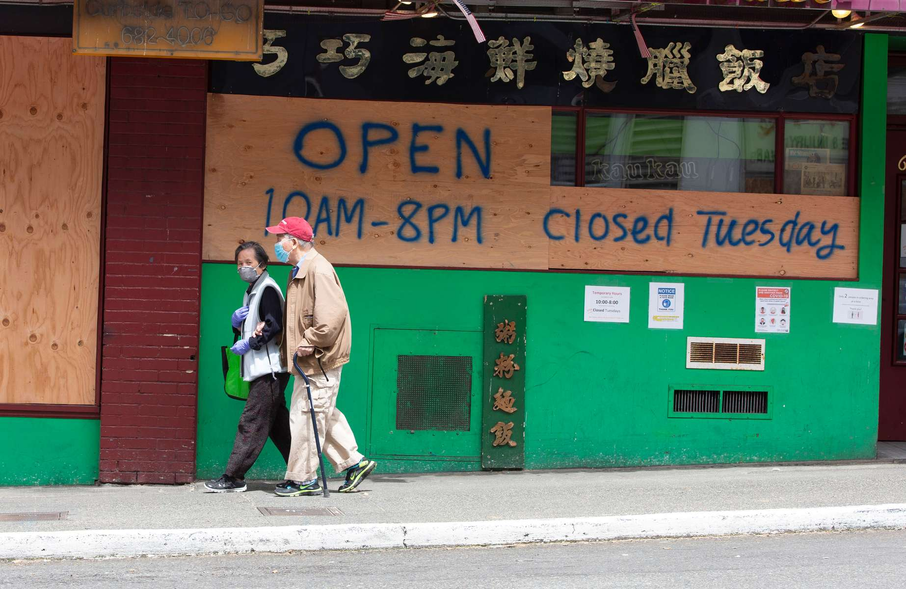 A couple walks past boarded up businesses in the Chinatown-International District in Seattle, WA on June 2, 2020. Businesses boarded up after a night of rioting swept up Jackson Street on May 29, 2020 and across the city the past couple of days. Protests around the country became violent after the killing of George Floyd, a black man in Minneapolis, who died while in the custody of white police officers, one of whom held him down with his knee. (Photo by Karen Ducey)