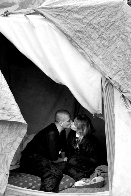 Johnnie Andersen kisses his fiancee in the tent they share with Andersen's father, Johnnie Andersen Sr. and his girlfriend, in Tent City #3 outside the Lake City Christian Church in Seattle. Tent cities are a growing West Coast phenomenom offering a temporary solution to the homeless problem, however Seattle, WA and Portland,OR are the only two municipalities in the United States to legally sanction them.
