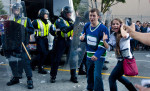 What's a party to some is serious business to others as Canuck's fans give a thumbs up while police appear concerned of the growing riot on the downtown streets of Vancouver, BC after the Canucks were defeated by the Boston Bruins in the Stanly Cup on June 15, 2011. (photo copyright Karen Ducey)