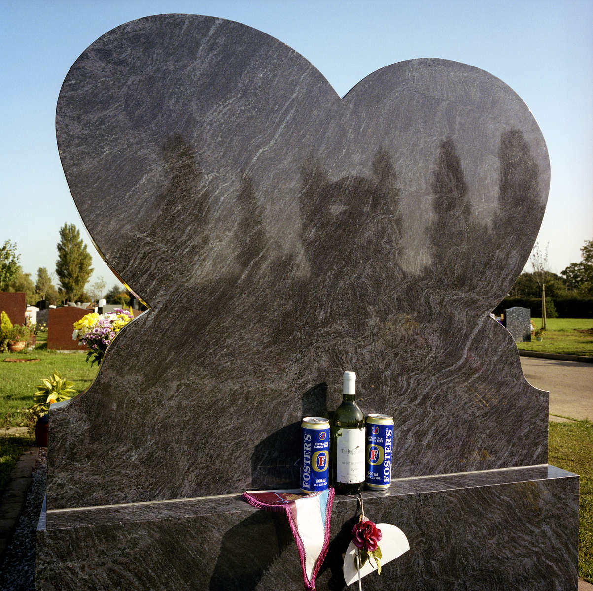 A bottle of The Dog's Bollocks white wine, two cans of Foster's lager and a West Ham United Football Club pennant placed on a memorial at a graveyard in Cheshunt. October 2001