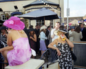 A woman dressed for Ladies Day drinks from a plastic pint glass outside a pub next to Royal Ascot Racecourse. June 2001