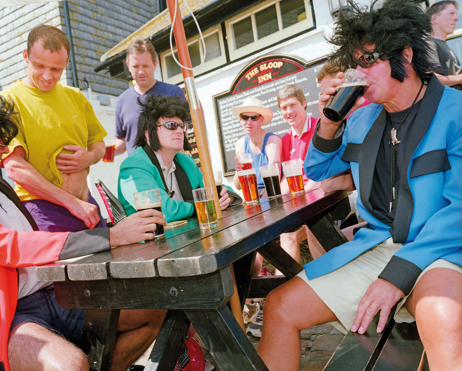 A group of friends in fancy dress drink outside the Sloop Inn in St Ives. May 2001